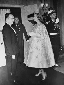 Original caption: Princess Grace And Rainier At Theater In Monaco. Monaco: Princess Grace of Monaco in Satin-Brocade evening coat, is shown with Prince Rainier III on their arrival for the opening of a new motion picture room at the